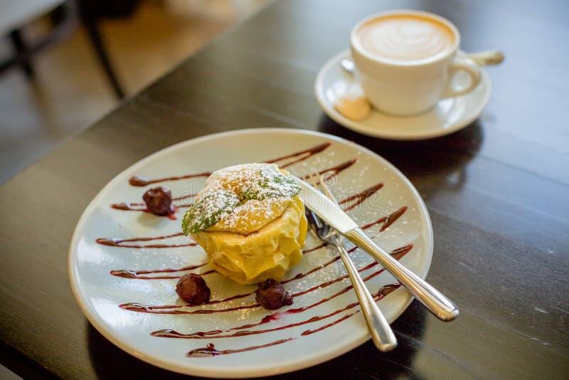 Испеченное яблоко с кофе сиропа и latte Испеченные яблоки с granola, циннамоном, гайками и медом Здоровый десерт плодоовощ тонизи стоковая фотография rf