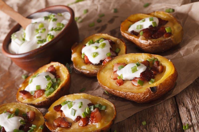 Испеченные кожи картошки с концом-вверх сыра, бекона и сметаны H стоковое изображение