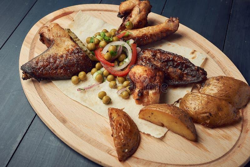 Испеченные крылья цыпленка с горохами и луком на деревянной плите стоковая фотография rf