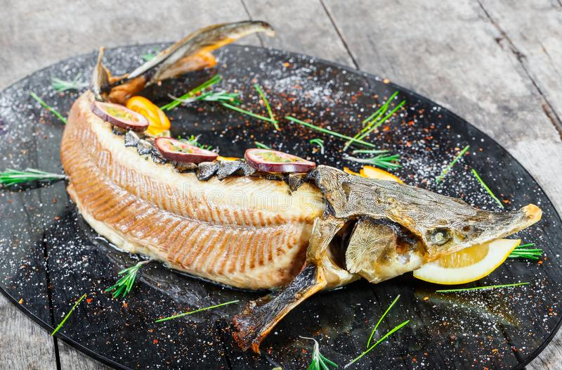 Испеченные рыбы стерляжины с розмариновым маслом, лимоном и маракуйей на плите на деревянном конце предпосылки вверх стоковые изображения rf