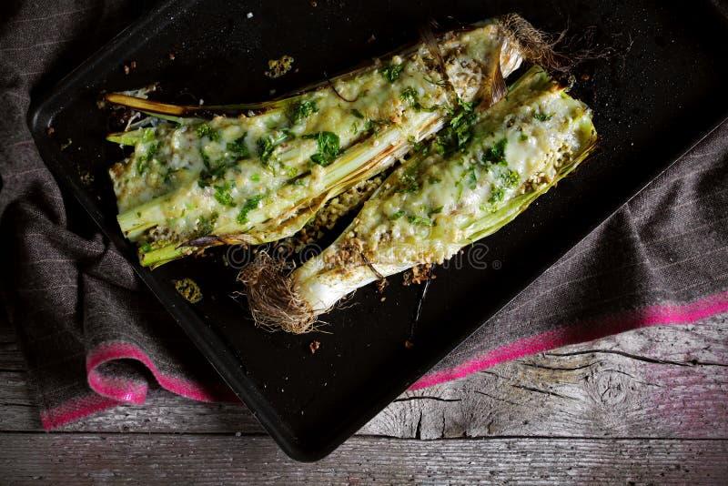Испеченные лук-пореи с сыром и петрушкой provolone итальянскими стоковое фото