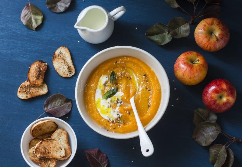 Испеченные яблоки и суп тыквы с мудрым маслом на голубой таблице взгляд сверху стоковая фотография