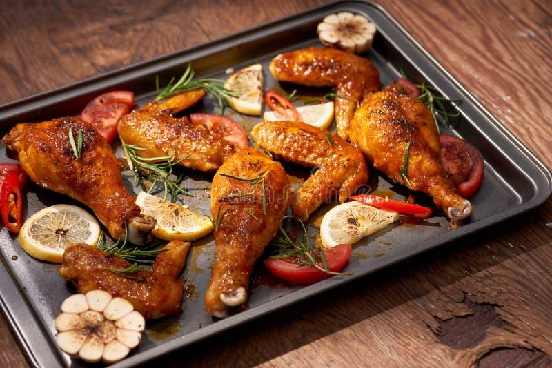 Испеченные drumstick и крыла цыпленка на подносе выпечки над темной деревянной предпосылкой стоковые фотографии rf