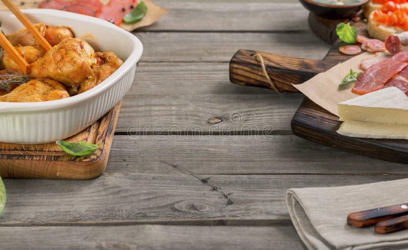 Испеченные drumsticks цыпленка с разнообразием закусок на деревянном столе стоковые фотографии rf