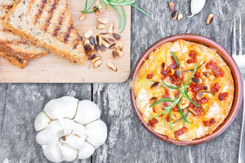 Испеченный камамбер с розмариновым маслом чеснока chorizo зажарил гайки сосны и стоковая фотография