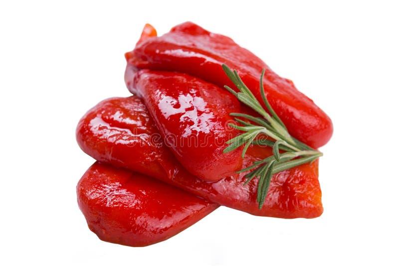 Испеченный красный болгарский перец, положенный вне в стог, украшенный с розмариновым маслом, на белую предпосылку стоковое фото