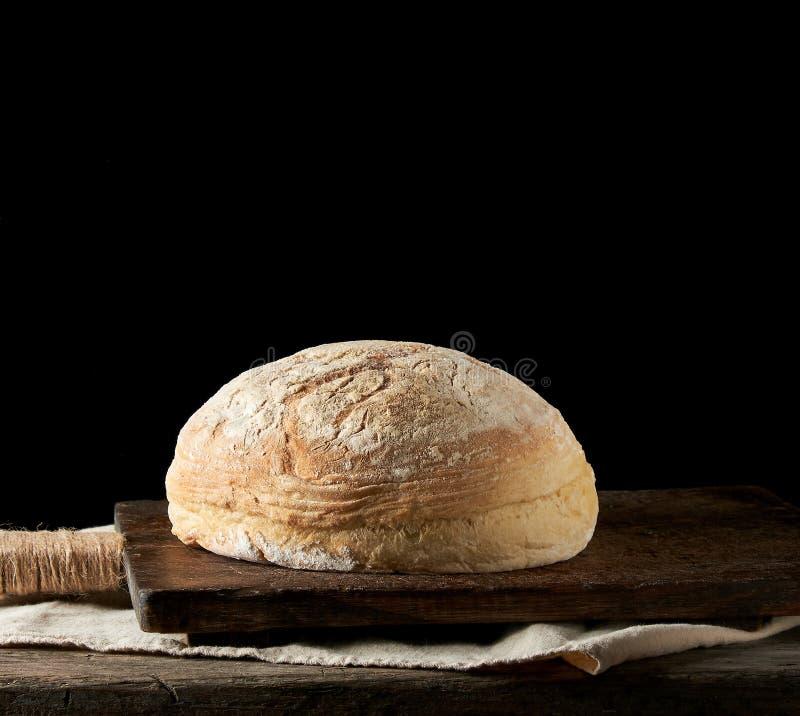 испеченный кругом белый хлеб на полотенце ткани, деревянная старая таблица пшеницы стоковые изображения