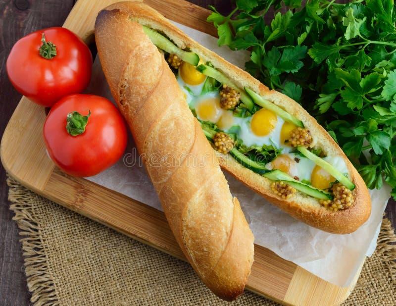 Испеченный кудрявый багет с яичницами, огурцами и зелеными цветами стоковые фотографии rf