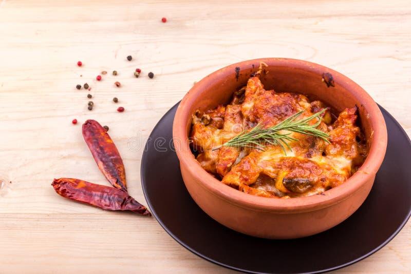 Испеченный цыпленок с грибами и сыром в глиняном горшке стоковая фотография