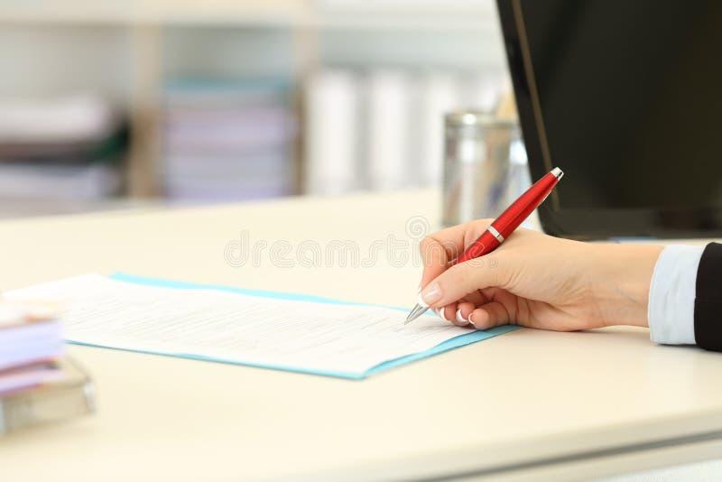 Исполнительная рука подписывая форму или контракт стоковые изображения