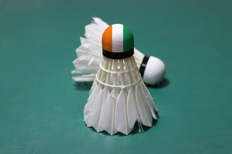 Используемое shuttlecock и на голове покрашенной с флагом Кот-д'Ивуар положило вертикальное и вне сфокусировать shuttlecock для у стоковые фотографии rf