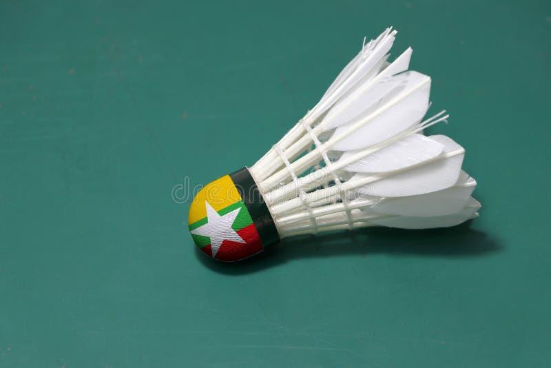 Используемое shuttlecock и на голове покрашенной с флагом Мьянмы положило горизонтальное на зеленый пол площадки для бадминтона стоковое изображение rf