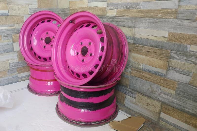 Используемый металл проштемпелевал оправы для автомобилей Выполненные на заказ розовые стальные колеса на предпосылке каменной ст стоковое изображение rf