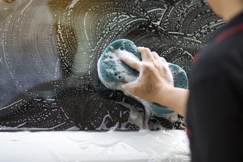 Используйте вашу правую руку для того чтобы уловить губку и отполировать окно автомобиля Мойка концепции стоковые фото