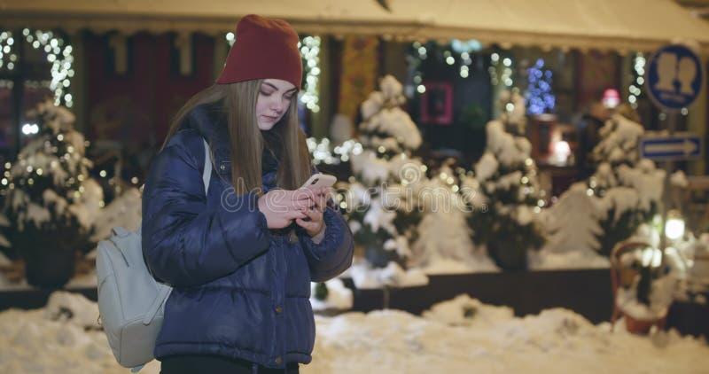 Используя мобильный телефон во время прогулки на улицах городка ночи стоковое фото