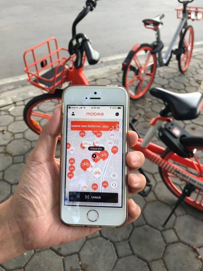 """Используя применение на iPhone для велосипеда  """"mobike†арендного который паркует на тропе около дороги стоковое фото"""