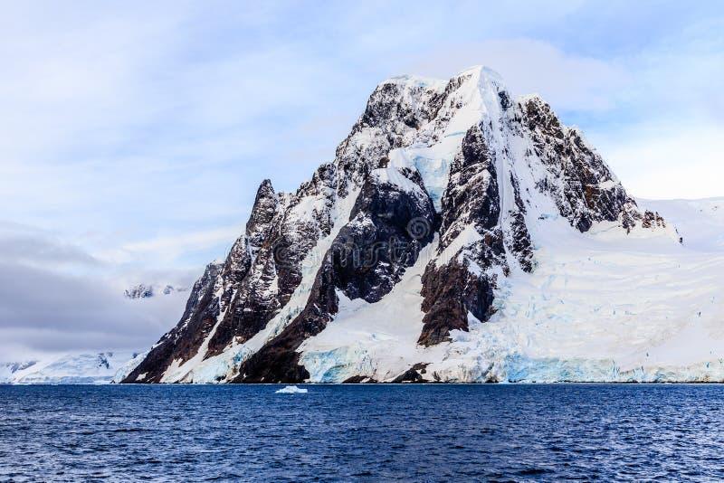 Исполинская крутая каменная скала покрытая с снегом и морем в foregrou стоковая фотография rf
