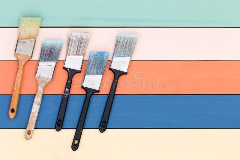 5 используемых paintbrushes на покрашенной деревянной панели стоковые изображения rf