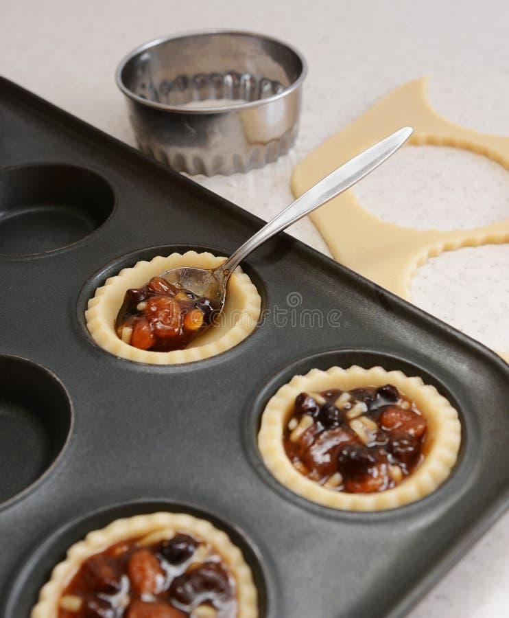 Используя чайную ложку для того чтобы заполнить случаи печенья с mincemeat стоковая фотография rf
