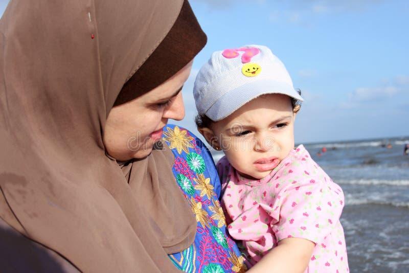 Испуганный арабский мусульманский ребёнок с ее матерью стоковое изображение