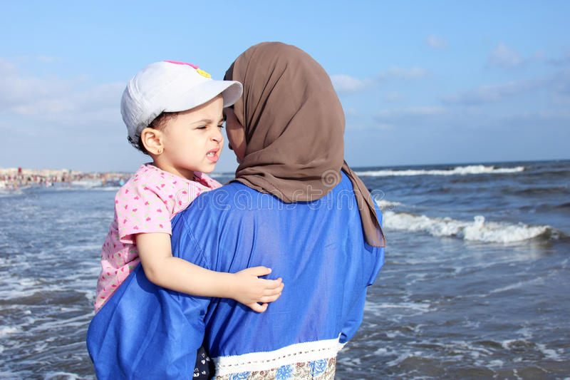 Испуганный арабский мусульманский ребёнок с ее матерью стоковое фото rf