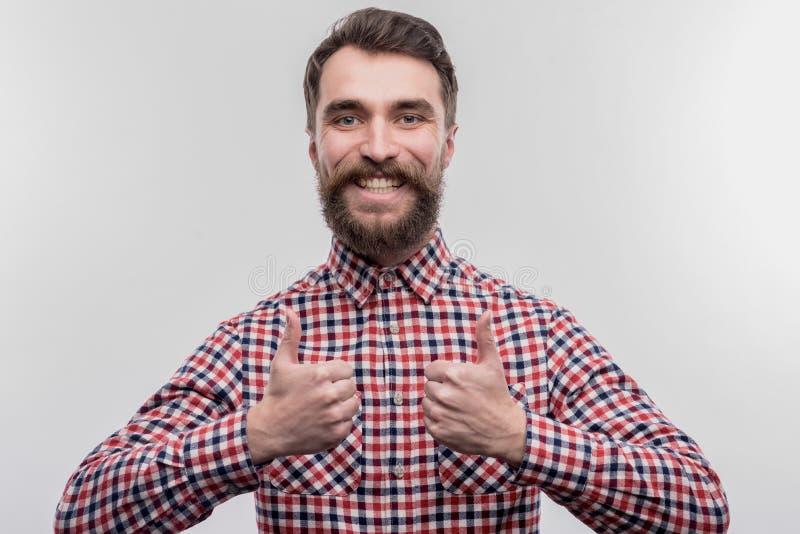 Испуская лучи бородатый темн-с волосами менеджер офиса чувствуя удовлетворяемый и жизнерадостный стоковые изображения rf