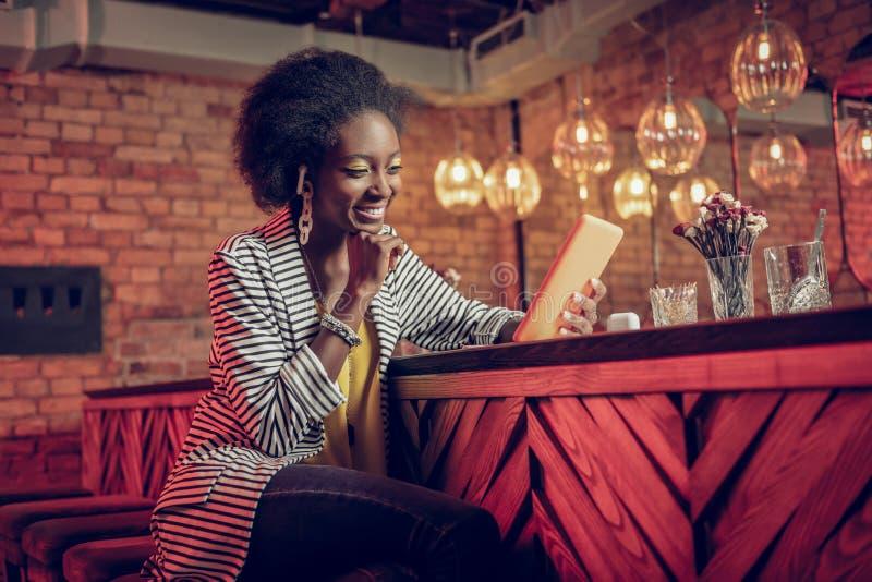 Испуская лучи женщина жизнерадостного молод-взрослого Афро-американская наслаждаясь веселым видео на планшете стоковое изображение