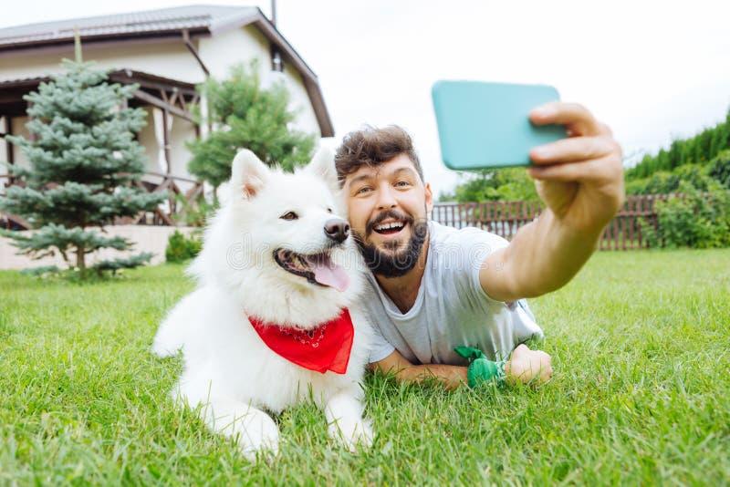 Испуская лучи красивый человек делая selfie с его белой лайкой стоковые фото