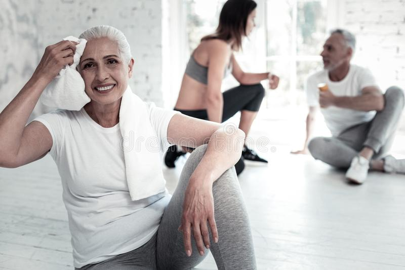 Испуская лучи старшая женщина grinning обширно во время тренировки стоковые фото