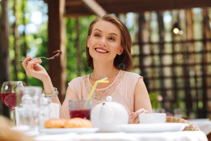 Испуская лучи стильная женщина есть сладостный торт стоковая фотография