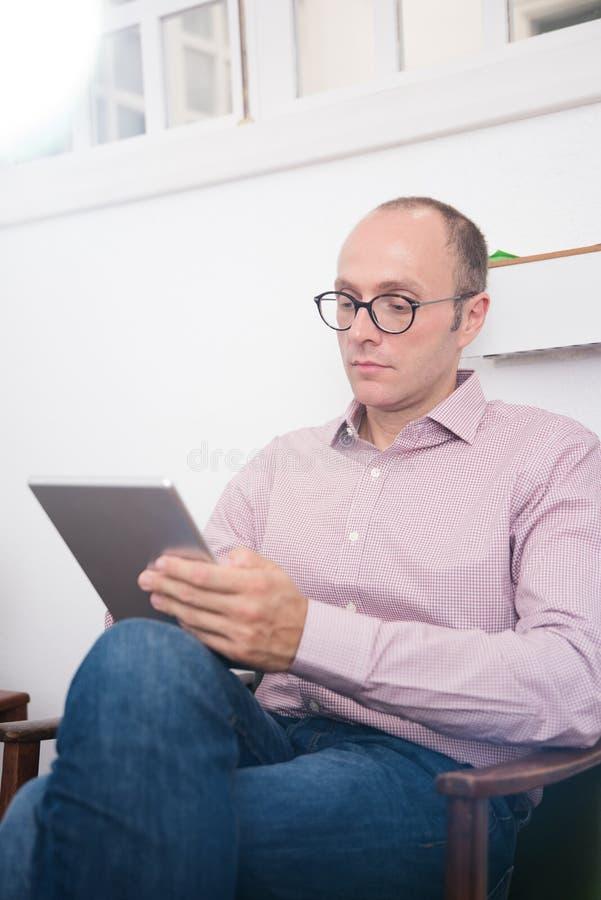 Испытание человека от таблетки ПК по мере того как он сидит в стуле стоковое изображение rf