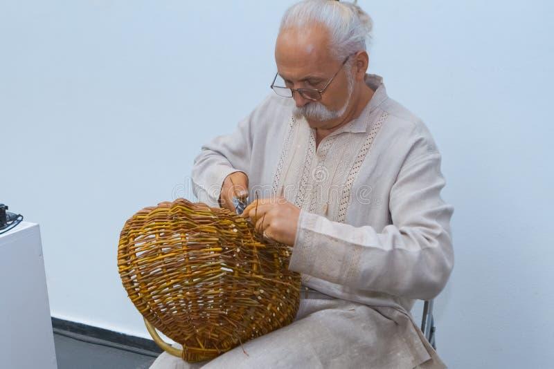 Испытанный мастер соткет корзину лозы вербы, последнего штриха, украинский этнический традиционный соткать стоковое фото rf