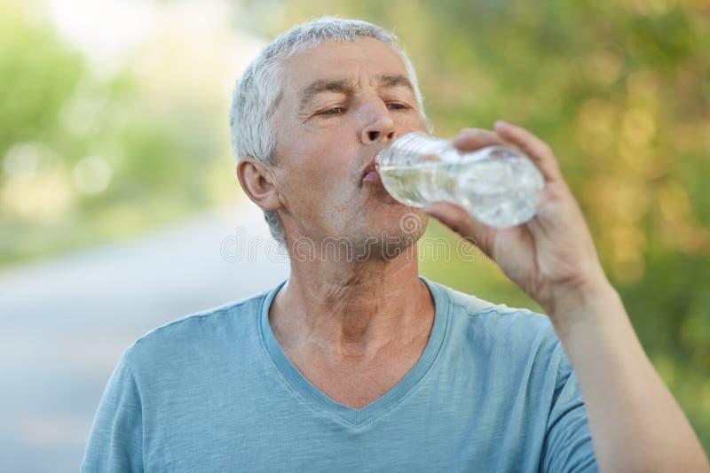 Испытывающий жажду старший мужчина выпивает воду от palstic бутылки, был утомлен после cardio тренировки, имеет активный образ жи стоковое фото