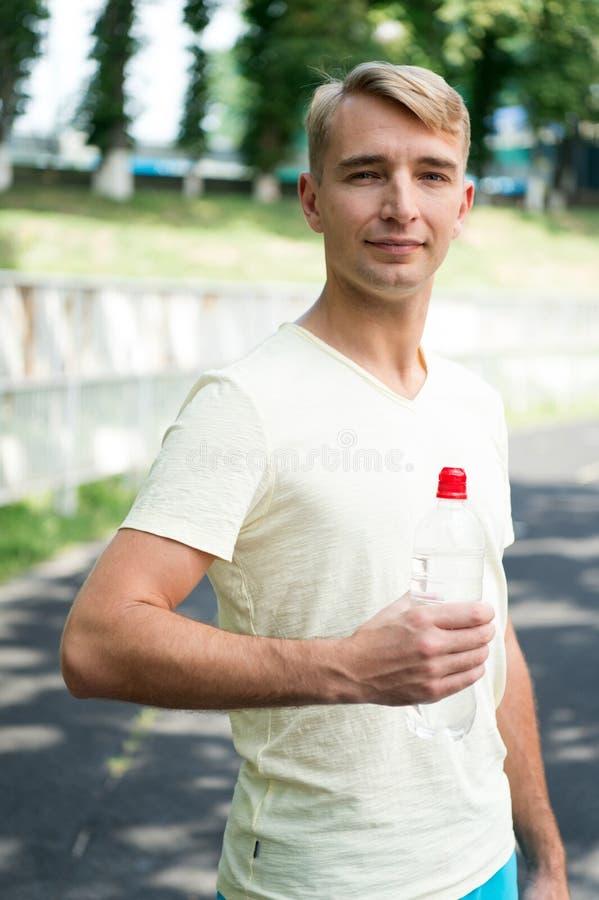Испытывающий жажду человек с бутылкой с водой на стадионе Спортсмен с пластичной бутылкой на солнечное внешнем Жажда и обезвожива стоковое фото rf