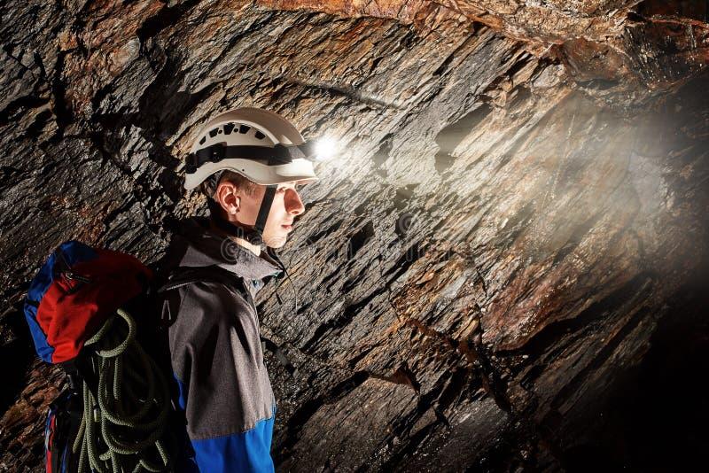 Исследование пещеры со шлемом и фарой стоковые фото