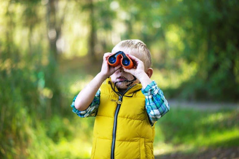 Исследователь мальчика молодой смотрит вверх и исследующ с bino стоковое изображение