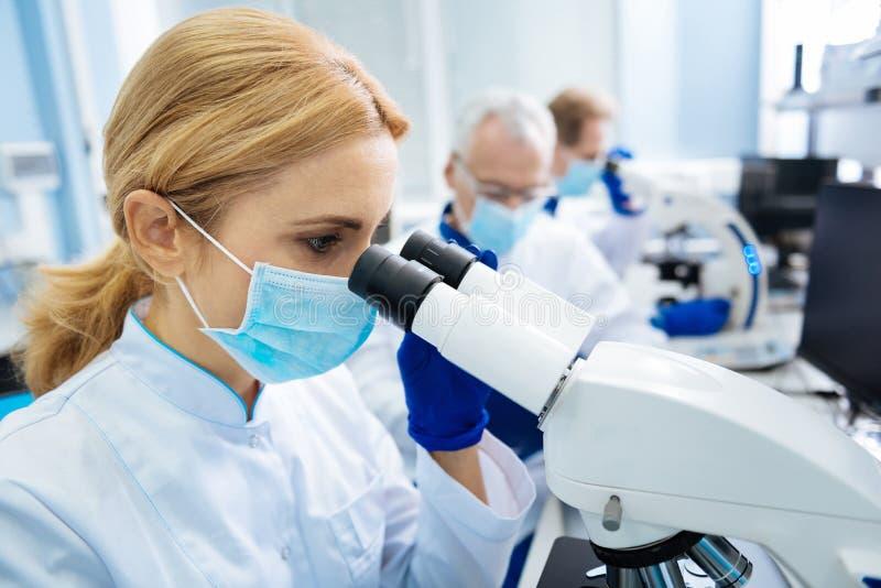 Исследователь работая с биотехнологиями в лаборатории стоковая фотография