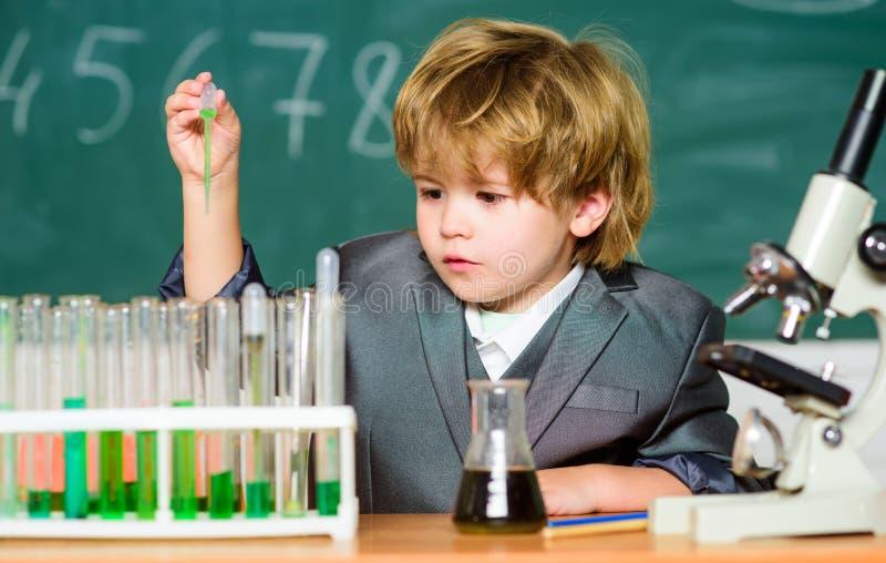 Исследуйте биологические молекулы Младенец гения малыша Мальчик около микроскопа и пробирок в классе школы Технология стоковые фотографии rf