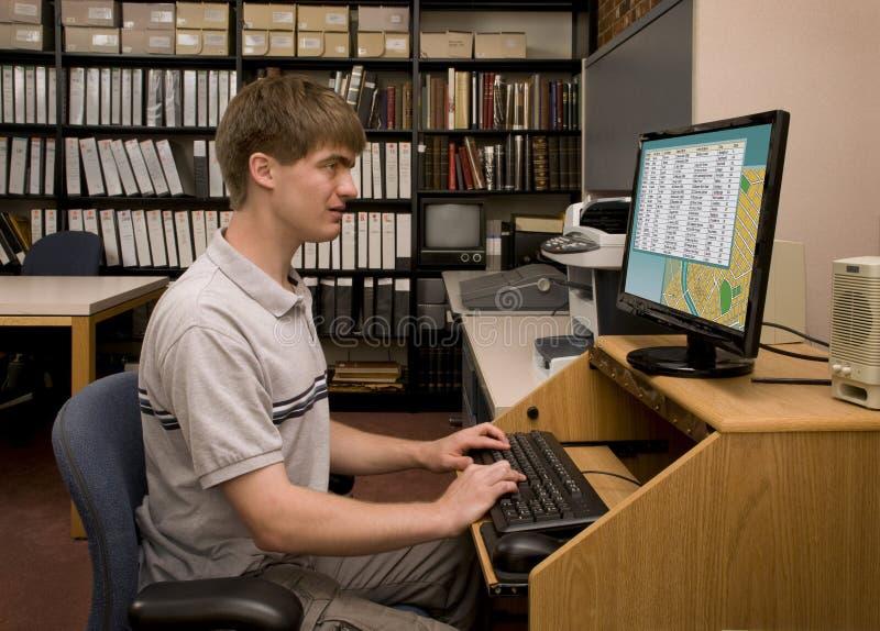 Исследование компьютера студента проводя в архиве библиотеки стоковое фото rf