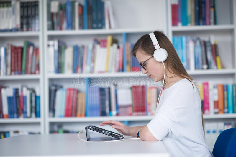 Исследование студентки в библиотеке, используя таблетку и искать для стоковые фотографии rf