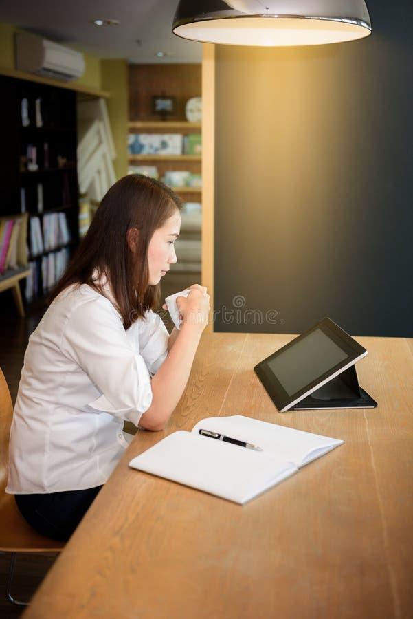 Исследование студентки в школьной библиотеке, используя таблетку, компьтер-книжка и стоковая фотография