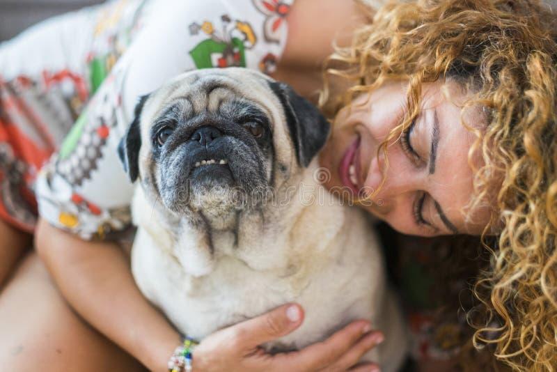 Истинная любовь между красивой кавказской женщиной и старым мопсом собаки, нечетными друзьями и концепцией семьи альтернативной ж стоковое изображение