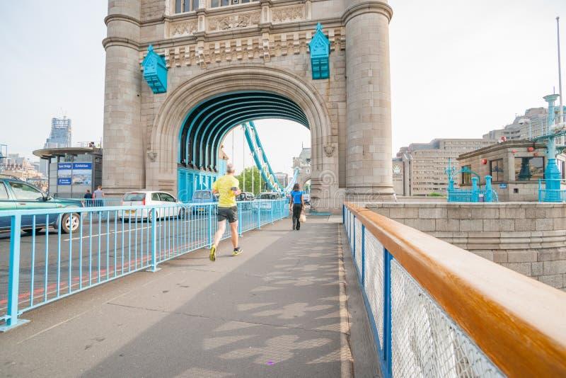 Историческая архитектура моста башни с женщиной идя впереди запачканного человека jogging поперек стоковое фото