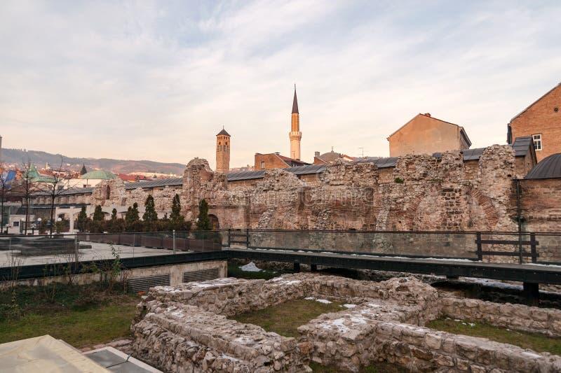 Исторические руины Taslihan с старыми башней вахты и минаретом мечети Gazi Husrev на стоковые изображения rf