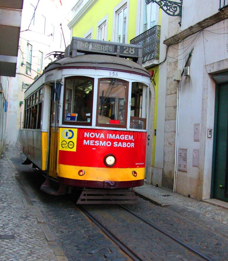 Исторический трамвай нет 28 между узким домом alfama Лиссабона, Португалия стоковое изображение rf