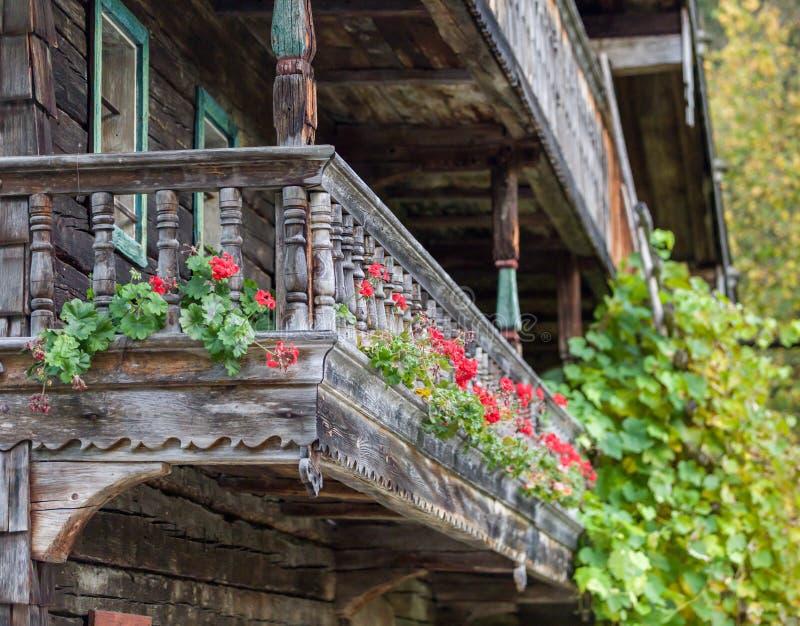 Исторический фронт сельского дома с красными гераниумами стоковая фотография