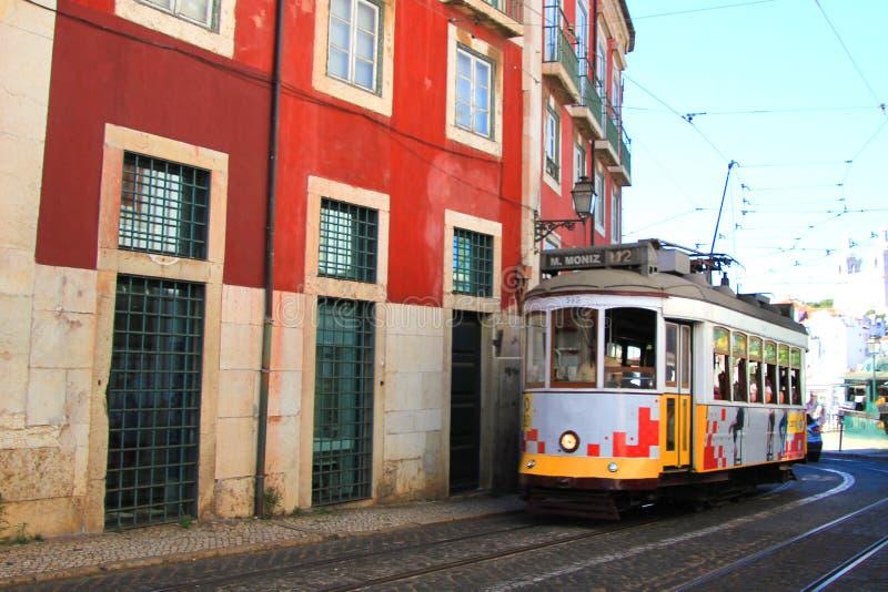Исторический электрический трамвай в улицах Лиссабона, Португалии, между старыми домами стоковое изображение rf