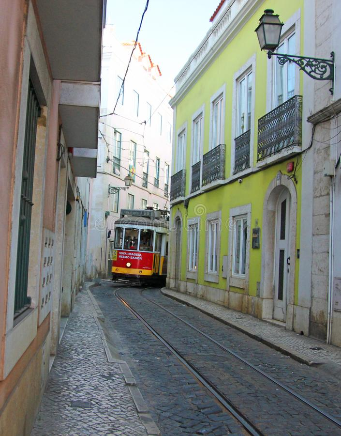 Исторический электрический трамвай нет 28 между узкими домами в Лиссабоне, Португалия стоковые изображения rf