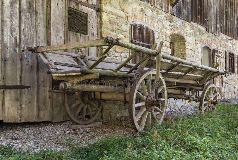 Исторической деревянной тележка управляемая лошадью перед старым сельским домом стоковая фотография rf