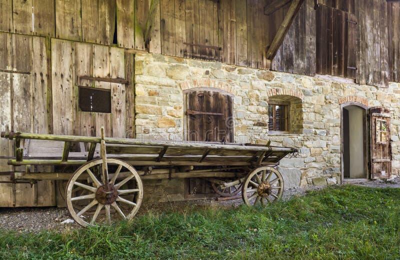 Исторической деревянной тележка управляемая лошадью перед старым сельским домом стоковые изображения